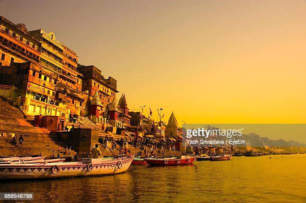 Boats Moored On Ganges River By Temples Against Clear Sky During Sunset