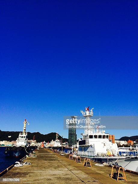 boats moored on harbor against clear blue sky - 北九州市 ストックフォトと画像