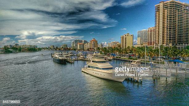 Boats Moored On Harbor By City Against Sky