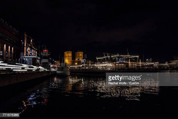 boats moored on illuminated city against sky at night - rachel wolfe stock pictures, royalty-free photos & images