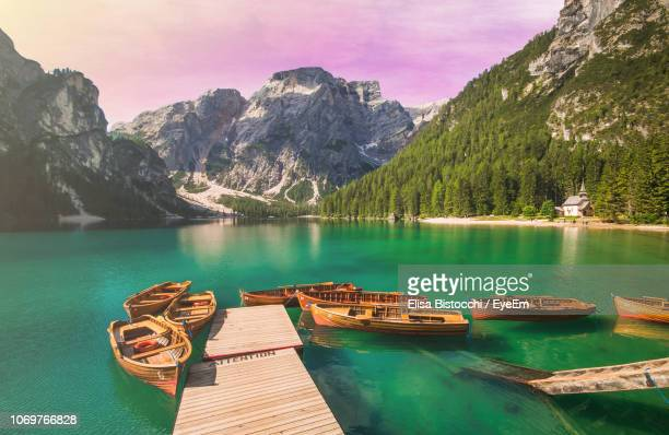 boats moored on lake against mountains - pragser wildsee stock pictures, royalty-free photos & images