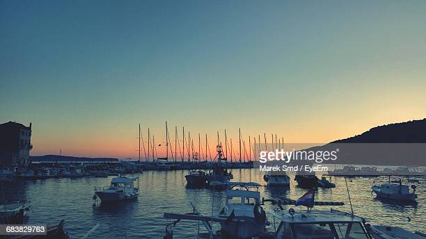 Boats Moored On Lake Against Sky During Sunset