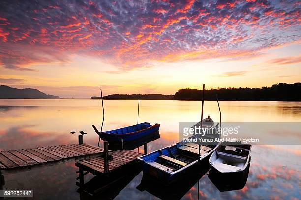 Boats Moored On River Against Dramatic Sky