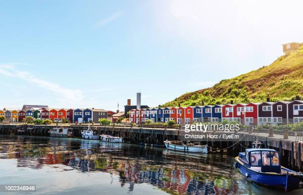 boats moored on river by buildings in city against sky - helgoland stock pictures, royalty-free photos & images