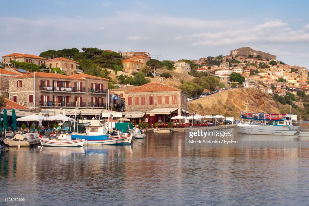 Boats Moored On River By Buildings In City Against Sky : Stock Photo