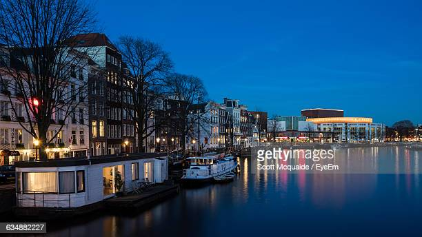 Boats Moored On River By Buildings In City