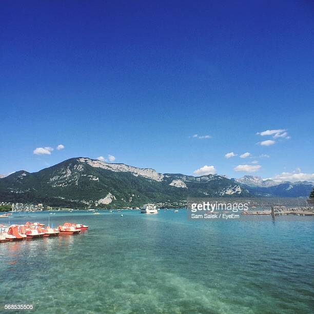 Boats Moored On River By Mountains Against Sky