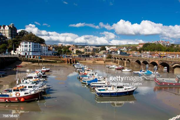 boats moored on river in city against sky - folkestone stock pictures, royalty-free photos & images
