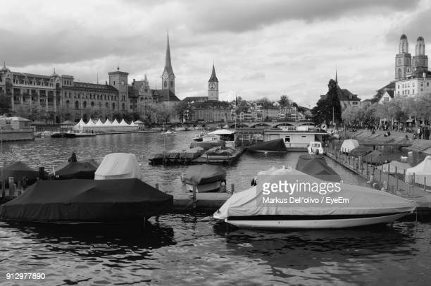 Boats Moored On River In City Against Sky