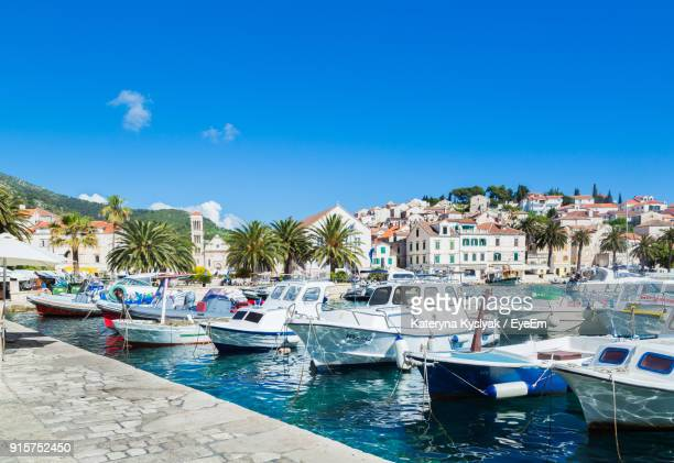 boats moored on sea against blue sky - hvar stock photos and pictures