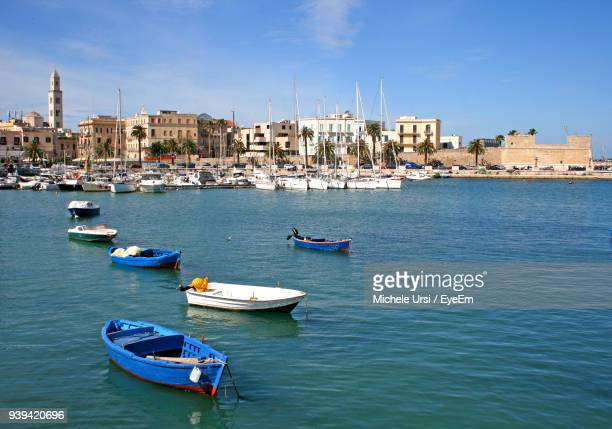 boats moored on sea against blue sky - bari stock photos and pictures