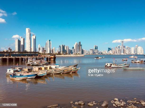 boats moored on sea against buildings in city - panama stock pictures, royalty-free photos & images