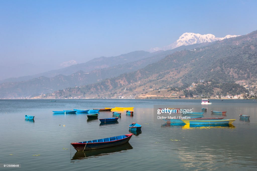 Boats Moored On Sea Against Clear Blue Sky : Stock Photo