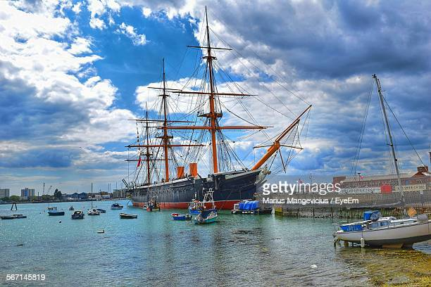 boats moored on sea against cloudy sky - portsmouth hampshire stock-fotos und bilder