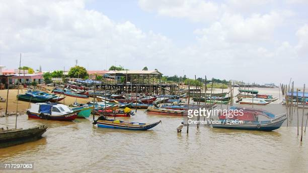 boats moored on sea against cloudy sky - guyana stock pictures, royalty-free photos & images