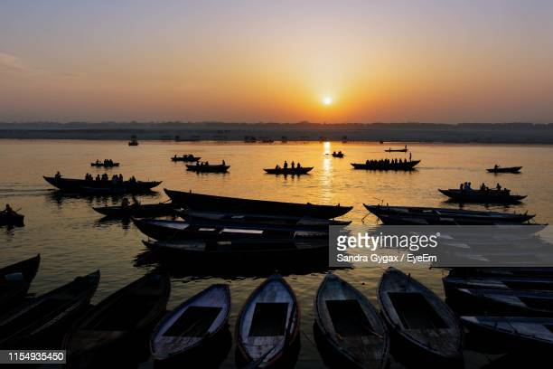 boats moored on sea against sky during sunset - sandra gygax stock-fotos und bilder