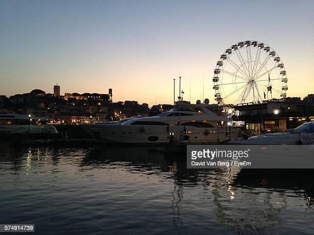 Boats Moored On Sea By Buildings During Sunset