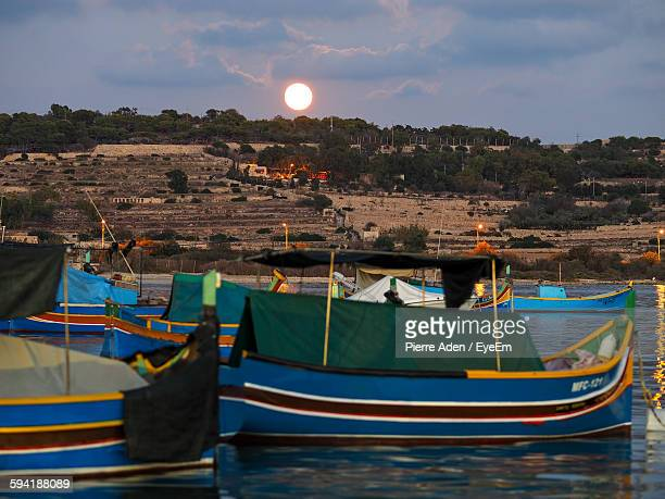 boats moored on sea by hill against sky - marsaxlokk stock pictures, royalty-free photos & images