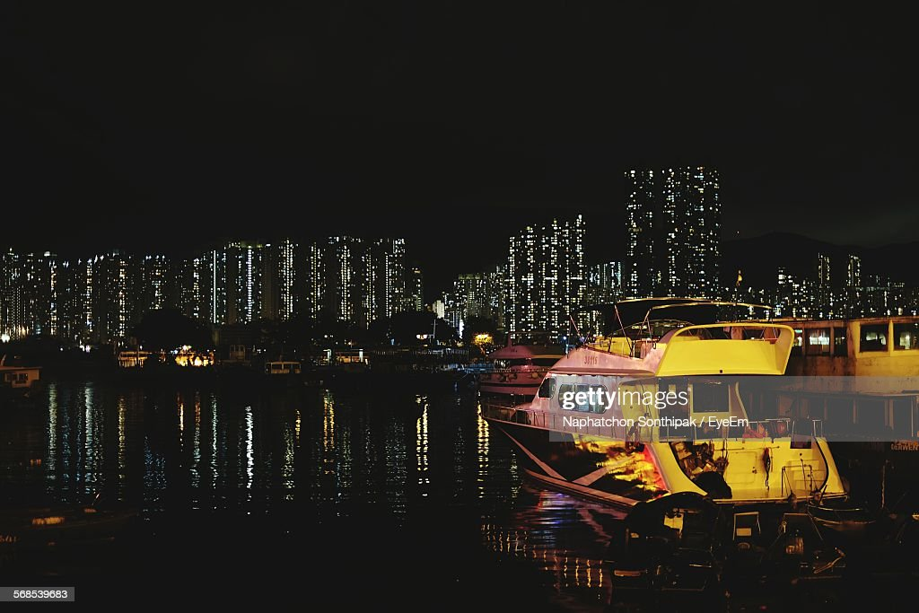 Boats Moored On Sea By Illuminated City Against Clear Sky At Night : Stock Photo