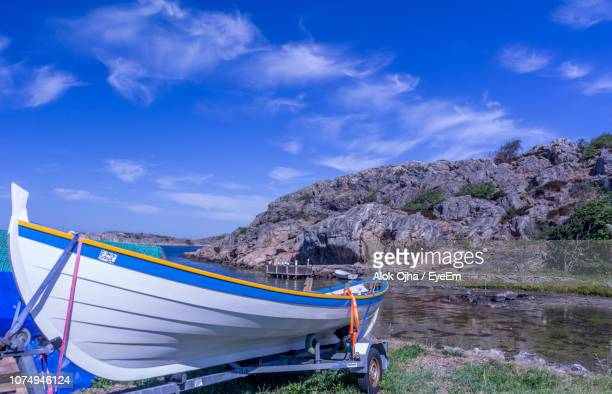 Boats Moored On Shore Against Blue Sky