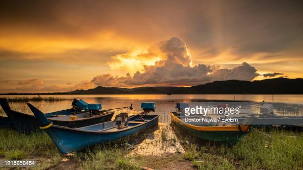 boats moored on shore against sky during sunset - lake sunset stock pictures, royalty-free photos & images