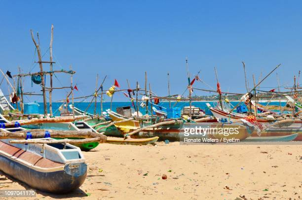 boats moored on shore at beach against clear blue sky - ゴール市 ストックフォトと画像