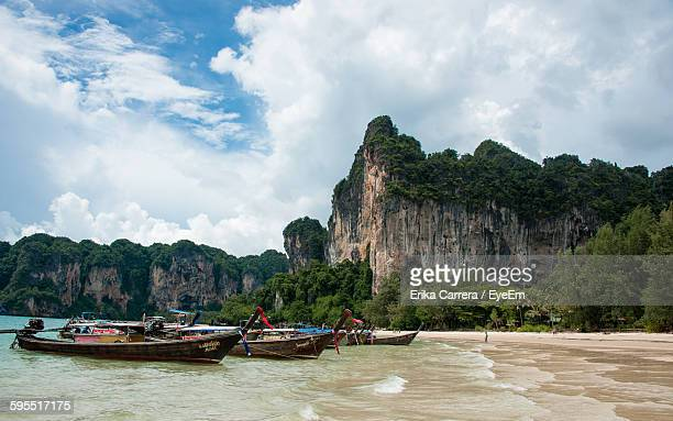 boats moored on shore by mountains against cloudy sky - asia carrera imagens e fotografias de stock