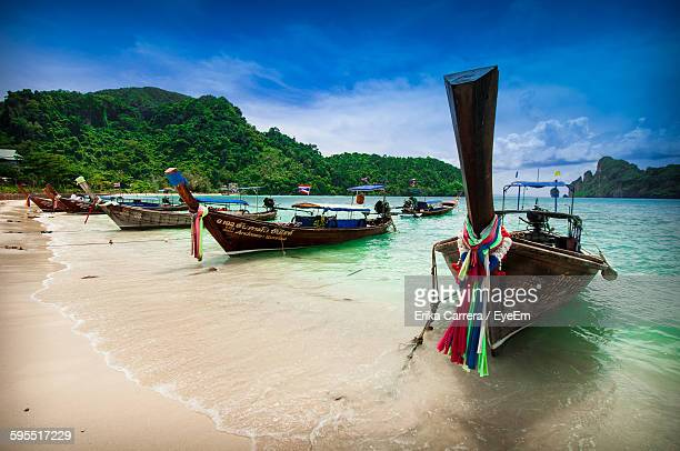 boats moored on shore by mountains against sky - asia carrera stock photos and pictures