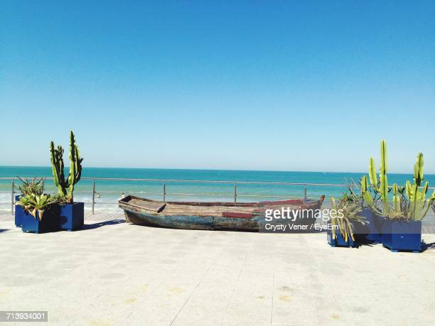 boats on beach against clear blue sky - maca plant stock photos and pictures