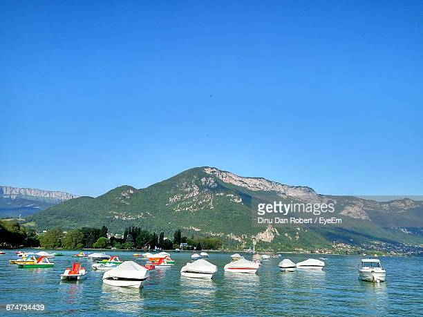 Boats On Lake By Mountain Against Clear Blue Sky