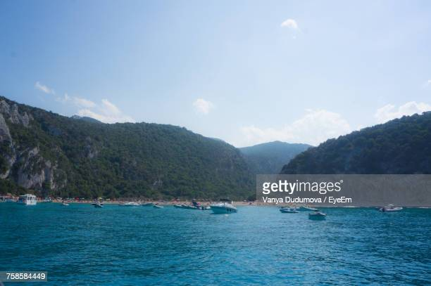 boats on mediterranean sea by mountains against sky at cala goloritze - cala goloritze foto e immagini stock