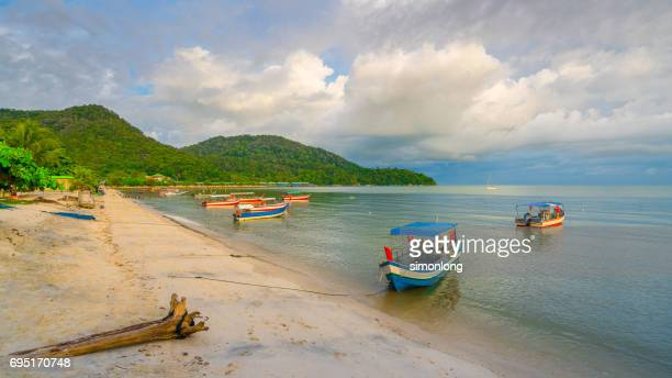 Boats on shore of tropical beach .