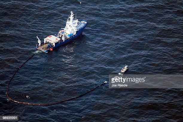 Boats pull an oil boom behind them as they skim the oil from the surface near where the Deepwater Horizon oil platform sank as work continues to...