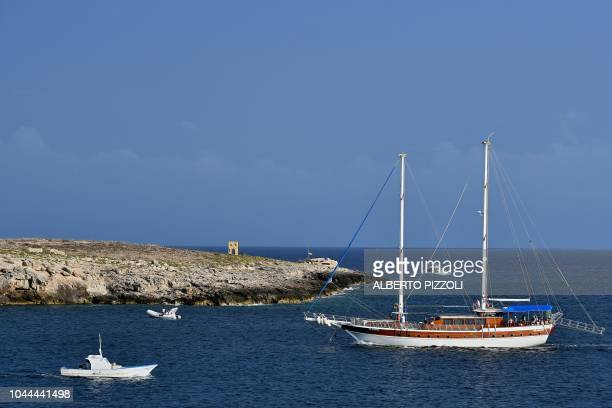 Boats sail off the Porta di Lampedusa known as The door of Europe a monument to the migrants who have died in the Mediterranean located at the point...