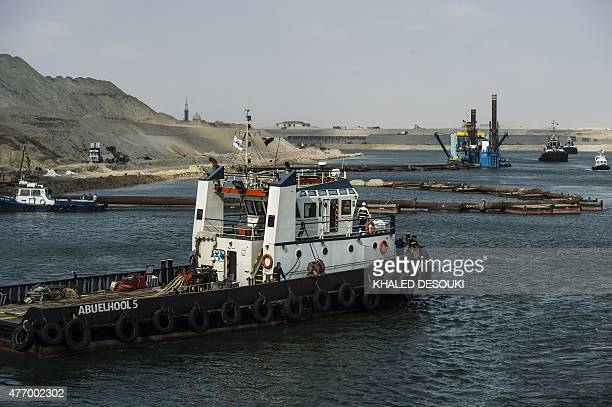 Boats sail past a dredger on the new waterway of the Suez canal on June 13 in the port city of Ismailia east of the capital Cairo Egypt will...