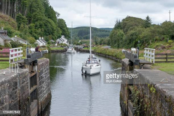Boats sail towards the sea locks at gate eight on the Crinan Canal on August 19, 2021 in Cairnbaan, Scotland. Passage along the canal has been...