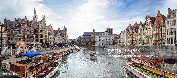 boats sailing in canal amidst buildings against cloudy sky - vgenopoulos stock pictures, royalty-free photos & images