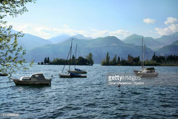 Boats Sailing In Lake Against Sky