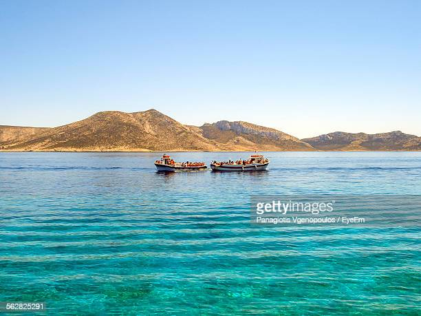 boats sailing in river in front of mountains against clear sky - vgenopoulos stock pictures, royalty-free photos & images