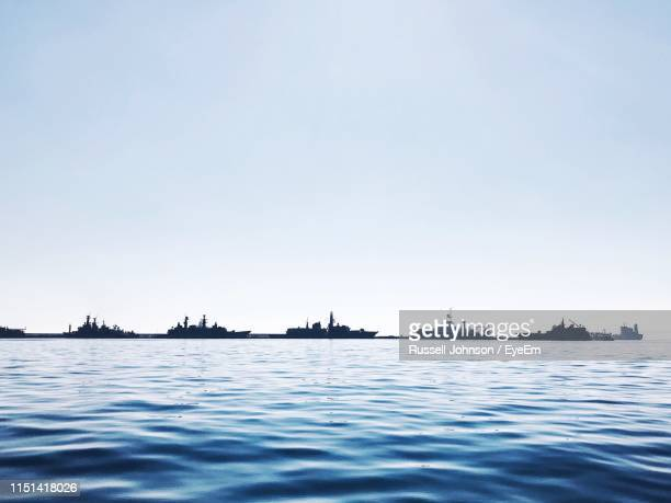 boats sailing in sea against clear sky - warship stock pictures, royalty-free photos & images