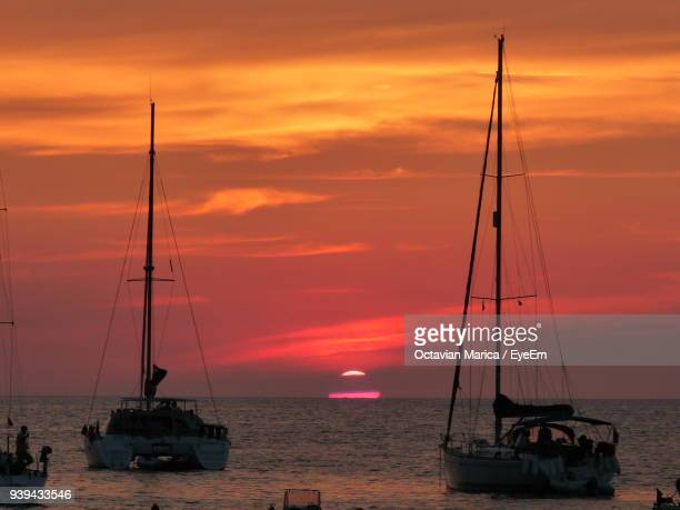 boats sailing in sea against sky during sunset - marica octavian stock photos and pictures