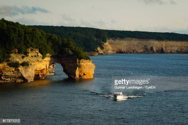 boats sailing in sea against sky - pictured rocks national lakeshore stock pictures, royalty-free photos & images