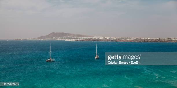 boats sailing in sea against sky - bortes stock photos and pictures