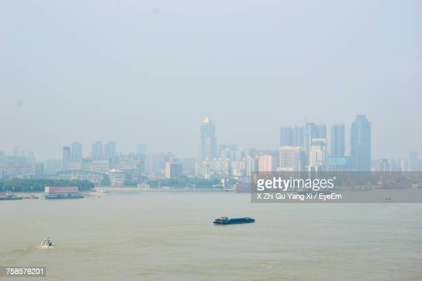 Boats Sailing In Sea By Cityscape Against Clear Sky
