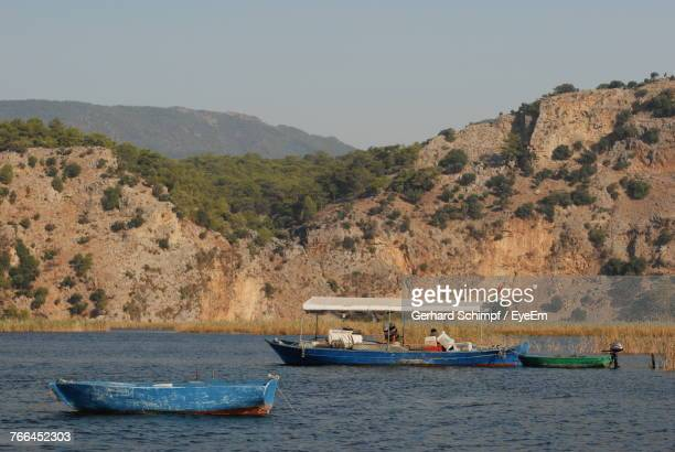 boats sailing on river by mountains against clear sky - gerhard schimpf stock photos and pictures