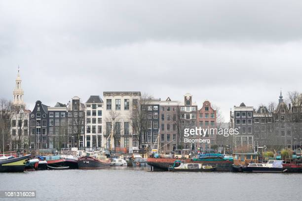 Boats sit moored alongside residential and commercial buildings in Amsterdam Netherlands on Friday Jan 11 2019 A large part of the latest buying wave...