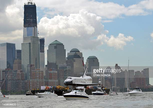 Boats surround the space shuttle Enterprise as it is towed by barge past lower Manhattan in New York June 6 2012 to the Intrepid Sea Air and Space...