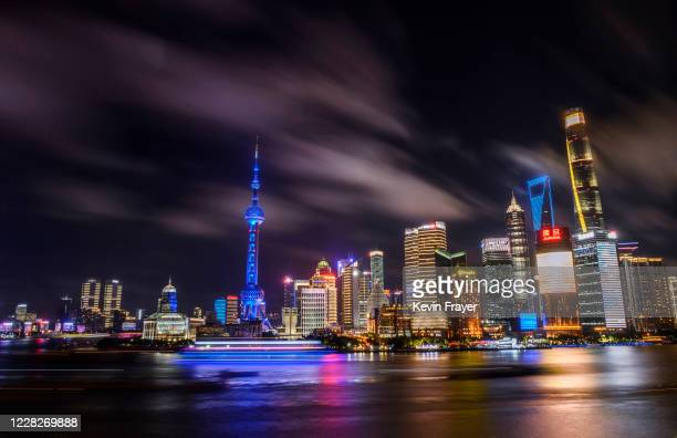 Boats travel on the Huangpu River as the skyline of the city in the Pudong district is seen on August 29, 2020 in Shanghai, China.