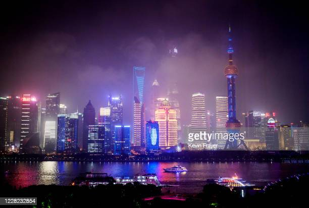 Boats travel on the Huangpu River as the skyline of the city is is seen in fog, including the Oriental Pearl TV Tower and the Shanghai Tower, on...