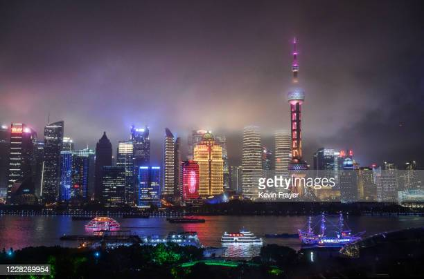 Boats travel on the Huangpu River as the skyline of the city is is seen, including the Oriental Pearl TV Tower and the Shanghai Tower, on August 28,...